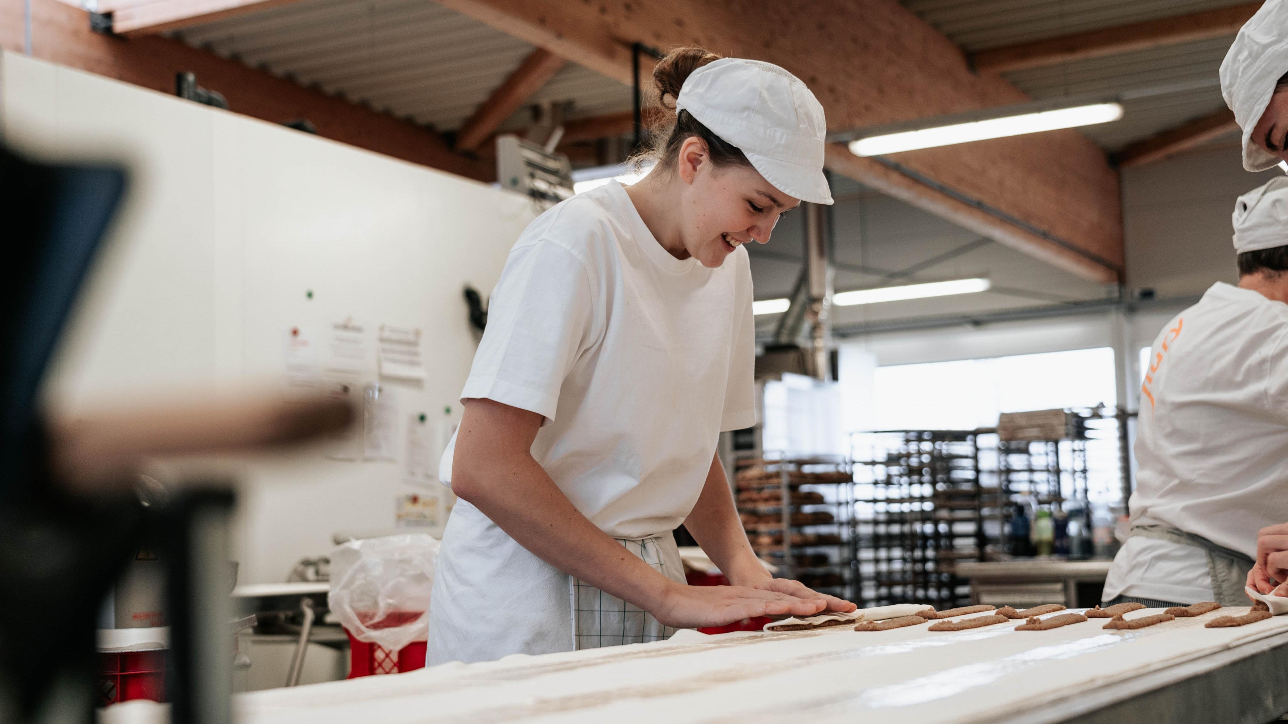 Bäckerin rollt eine Nussstange zusammen und lacht dabei.