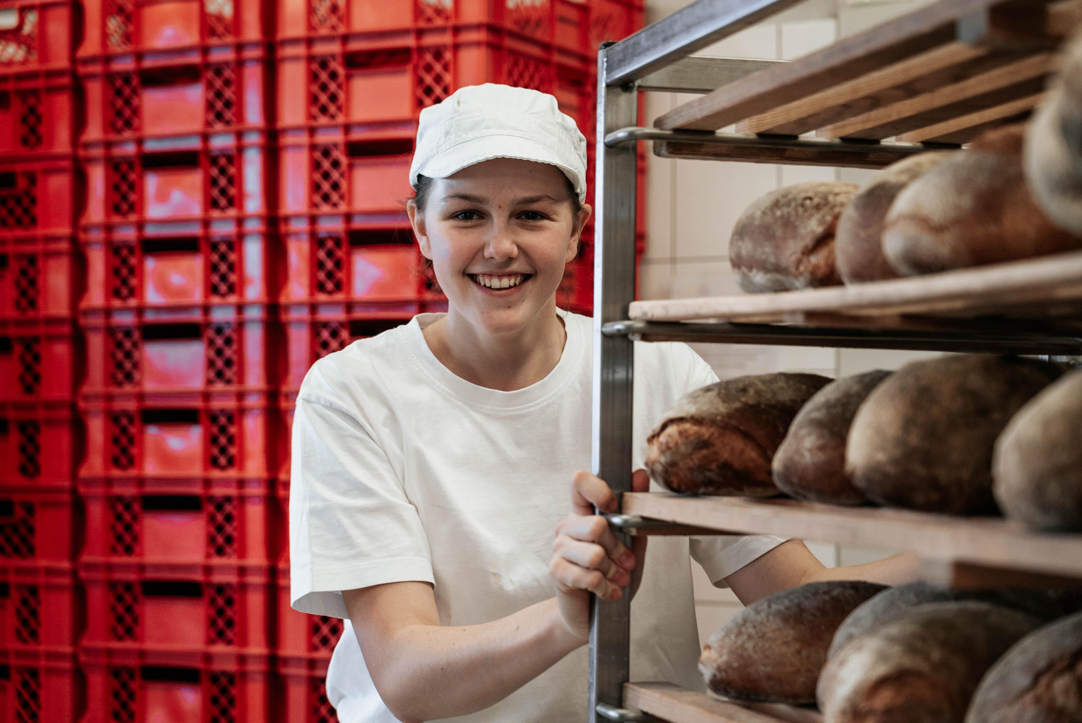 Bäckerin schiebt einen Wagen mit Brot.