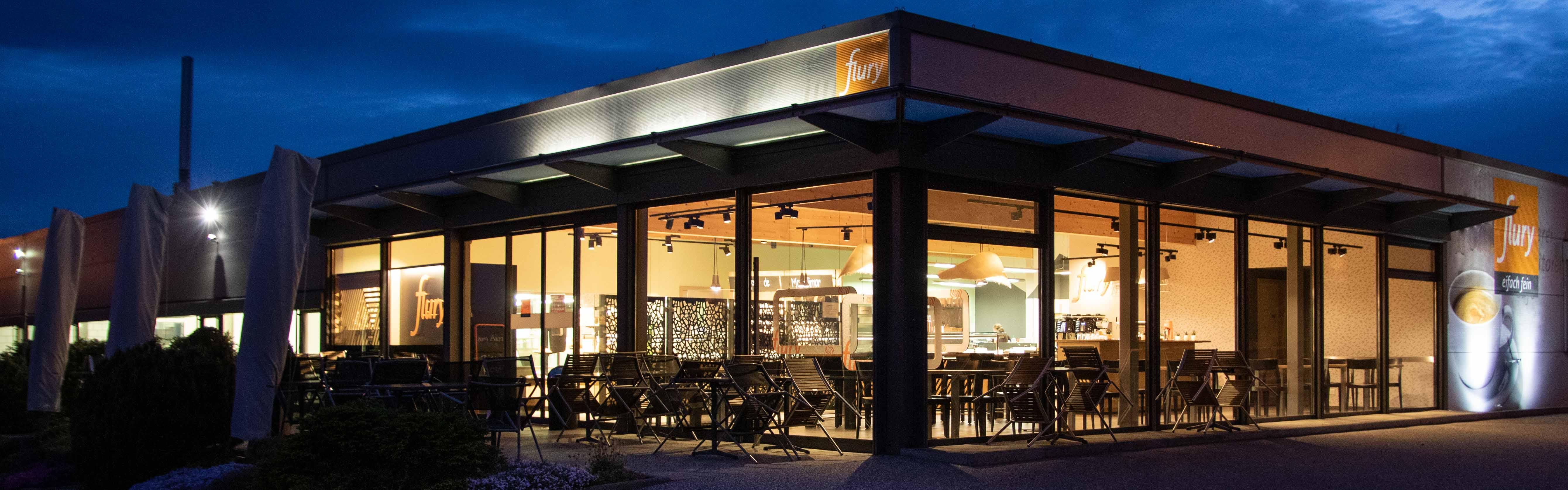 Ein Flury Café ist am Morgen bei Dunkelheit bereits beleuchtet.